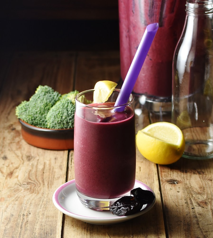 Berry broccoli smoothie in glass with purple straw on top of white saucer with prunes, lemon, broccoli and smoothie in blender in background.