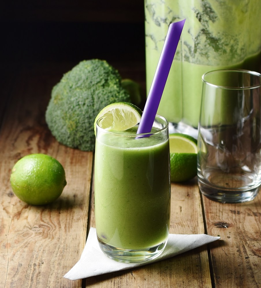 Side view of green broccoli smoothie in glass with purple straw on top of folded napkin, with lime, broccoli, smoothie in blender and empty glass in background.
