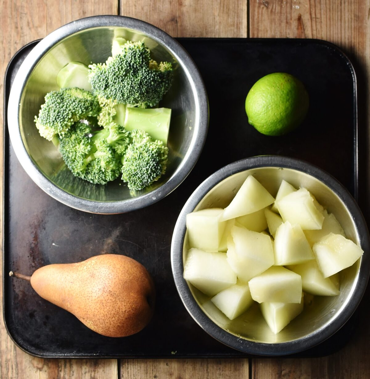 Chopped melon and broccoli in separate metal bowls, pear and lime on top of black tray.