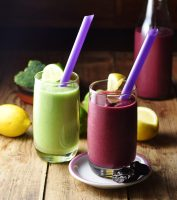 Purple and green broccoli smoothies with purple straws and lemon in background.