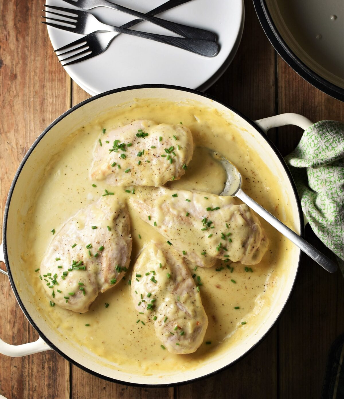 4 chicken breasts with chopped chives in large shallow white pan with spoon, green cloth to the right and plates with forks at the top.