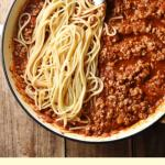 Spaghetti bolognese in large shallow white dish with fork and grated cheese in small dish in background.