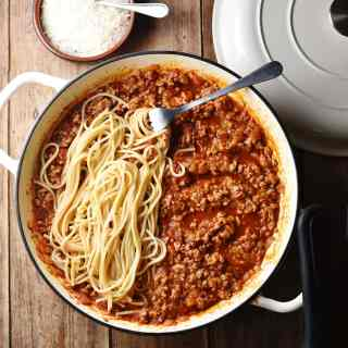Top down view of turkey bolognese sauce with spaghetti and fork in large white shallow dish, with grated cheese in small dish and white lid in background.