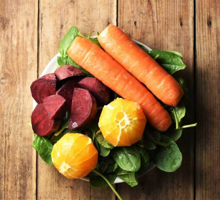 Cubed beet, 2 carrots, 2 peeled oranges on top of spinach leaves.