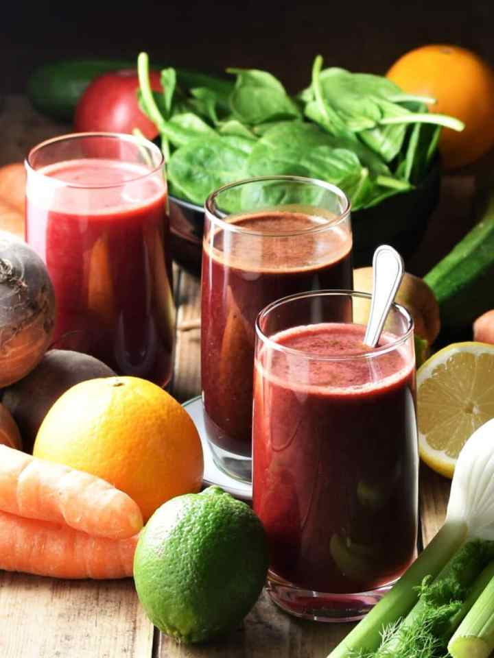 3 glasses of dark beetroot juice with fresh vegetables and fruits in background.