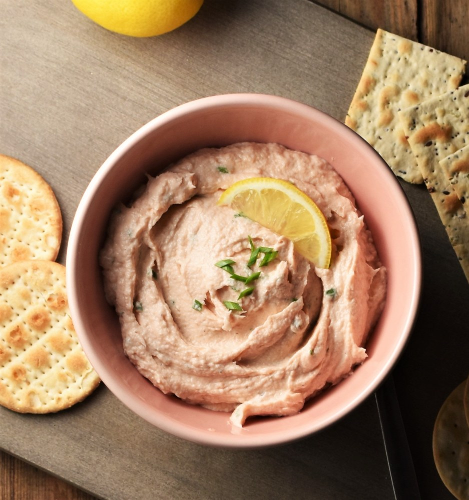 Creamy salmon spread in pink bowl with crackers and lemon on top of grey wooden board.