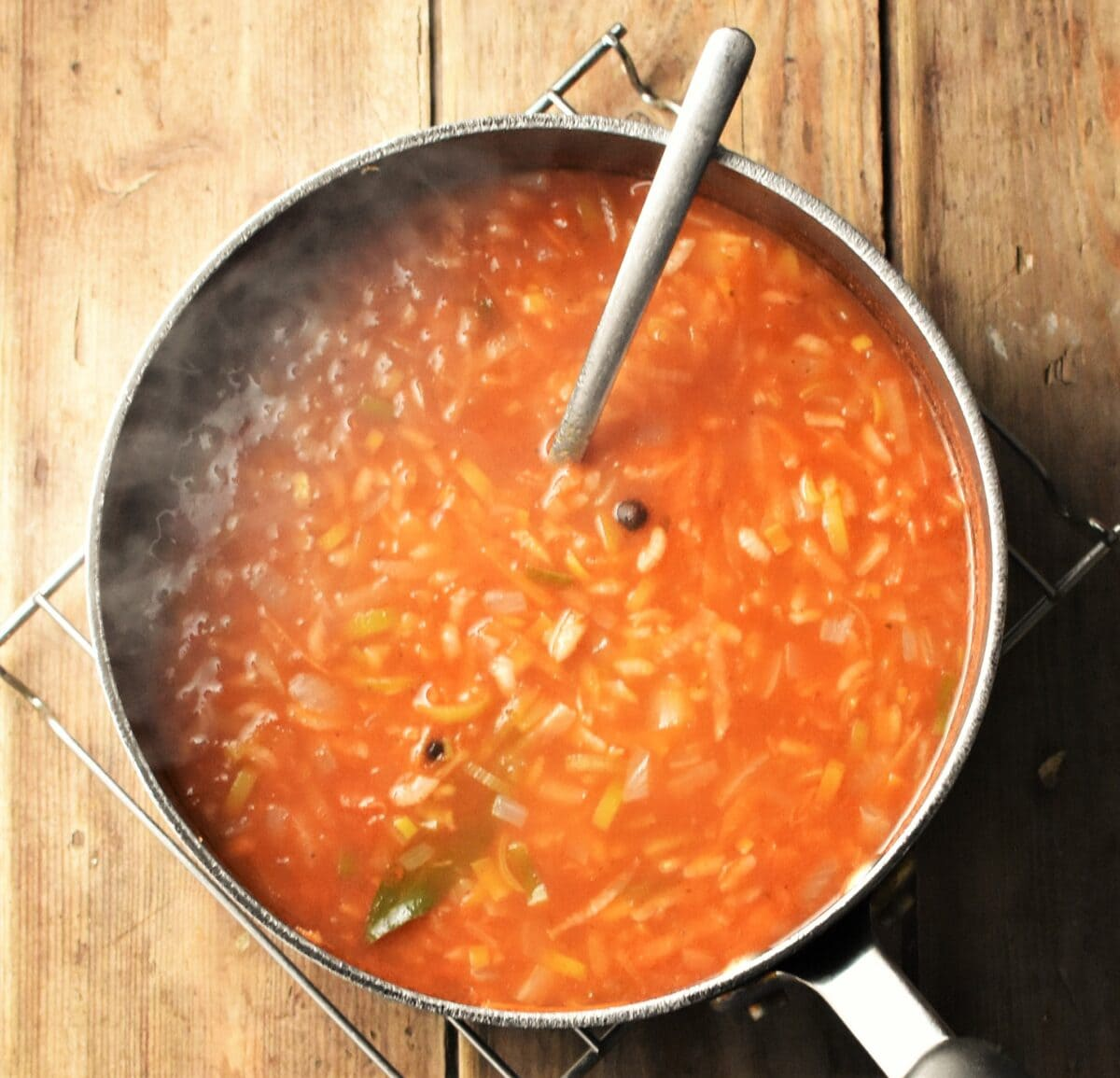 Steaming tomato and rice soup with vegetables in large pot with spoon.