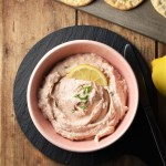 Creamy salmon spread with lemon slice in pink bowl on black plate with crackers and lemon in background.