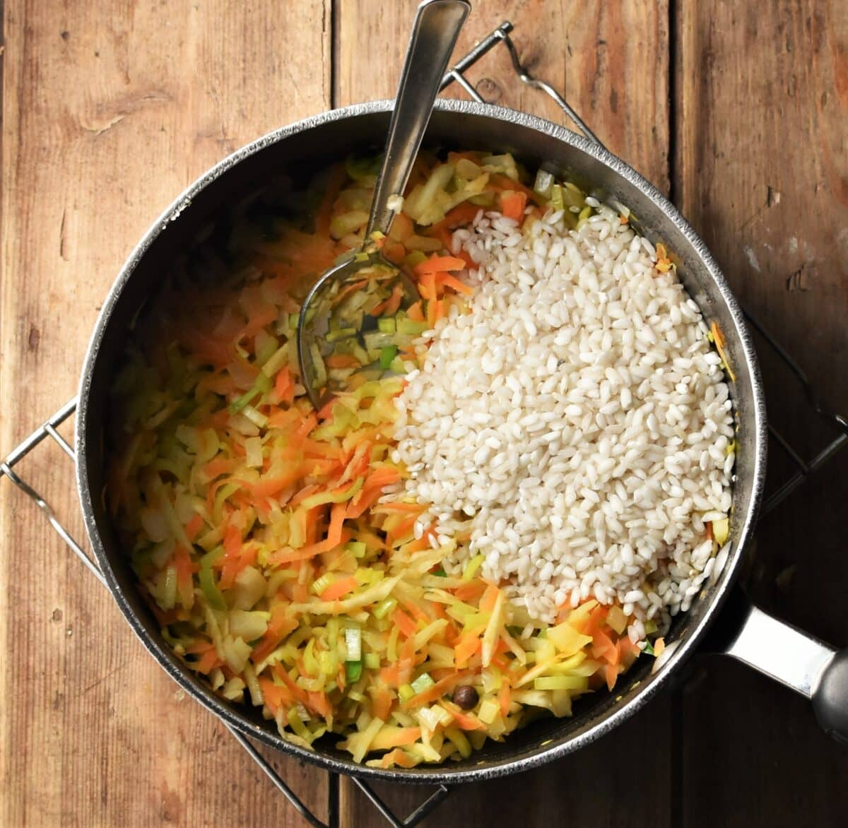 Grated vegetables and rice on large pot with spoon.