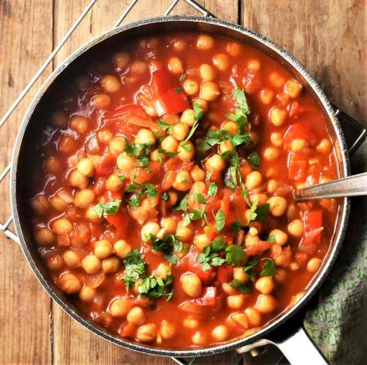 Top down view of chickpea casserole with parsley in pot with spoon.