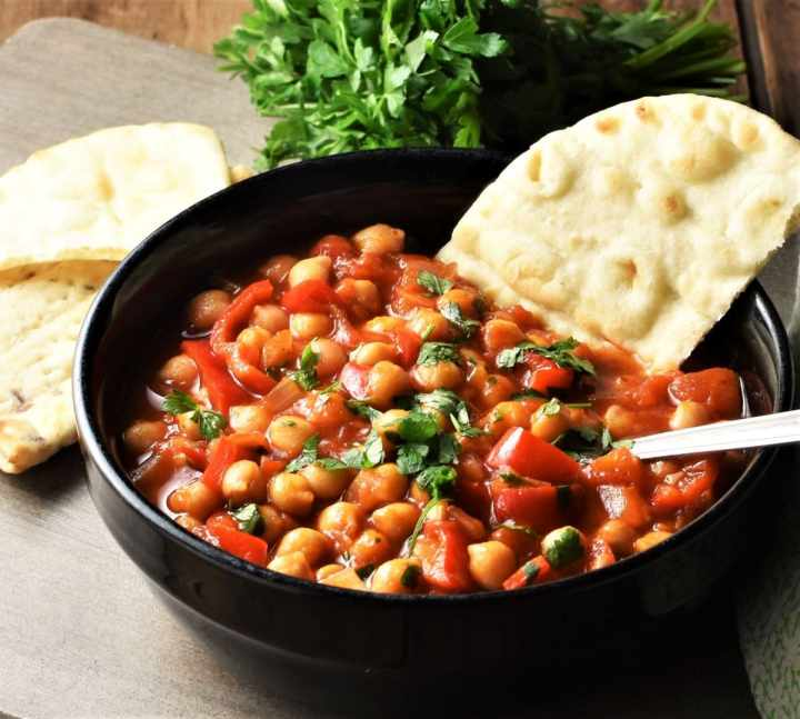Side view of chickpea stew in black bowl with pita and parsley in background.