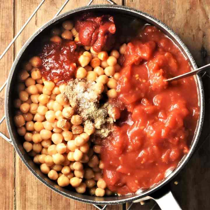 Tomato sauce and chickpeas with spices in pot with spoon.
