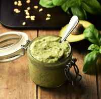 Side view of avocado pesto in jar with spoon, avocado, basil and pine nuts in background.