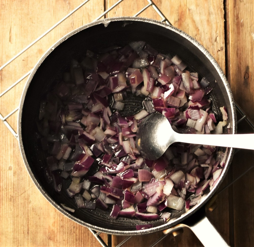 Chopped red onion in large pot with spoon.