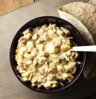 Creamy chicken pineapple salad in purple bowl with spoon and wrap in background.