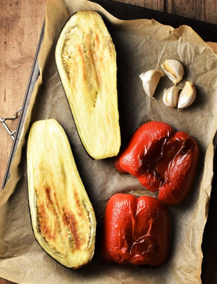 Top down view of roasted eggplant and red pepper with 4 garlic cloves on parchment.