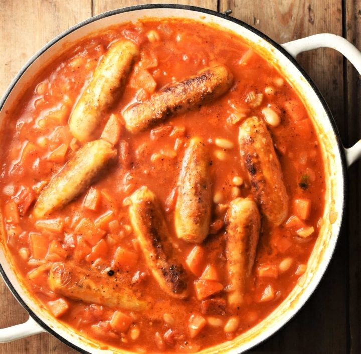 Sausages and beans in tomato sauce in shallow white pan.