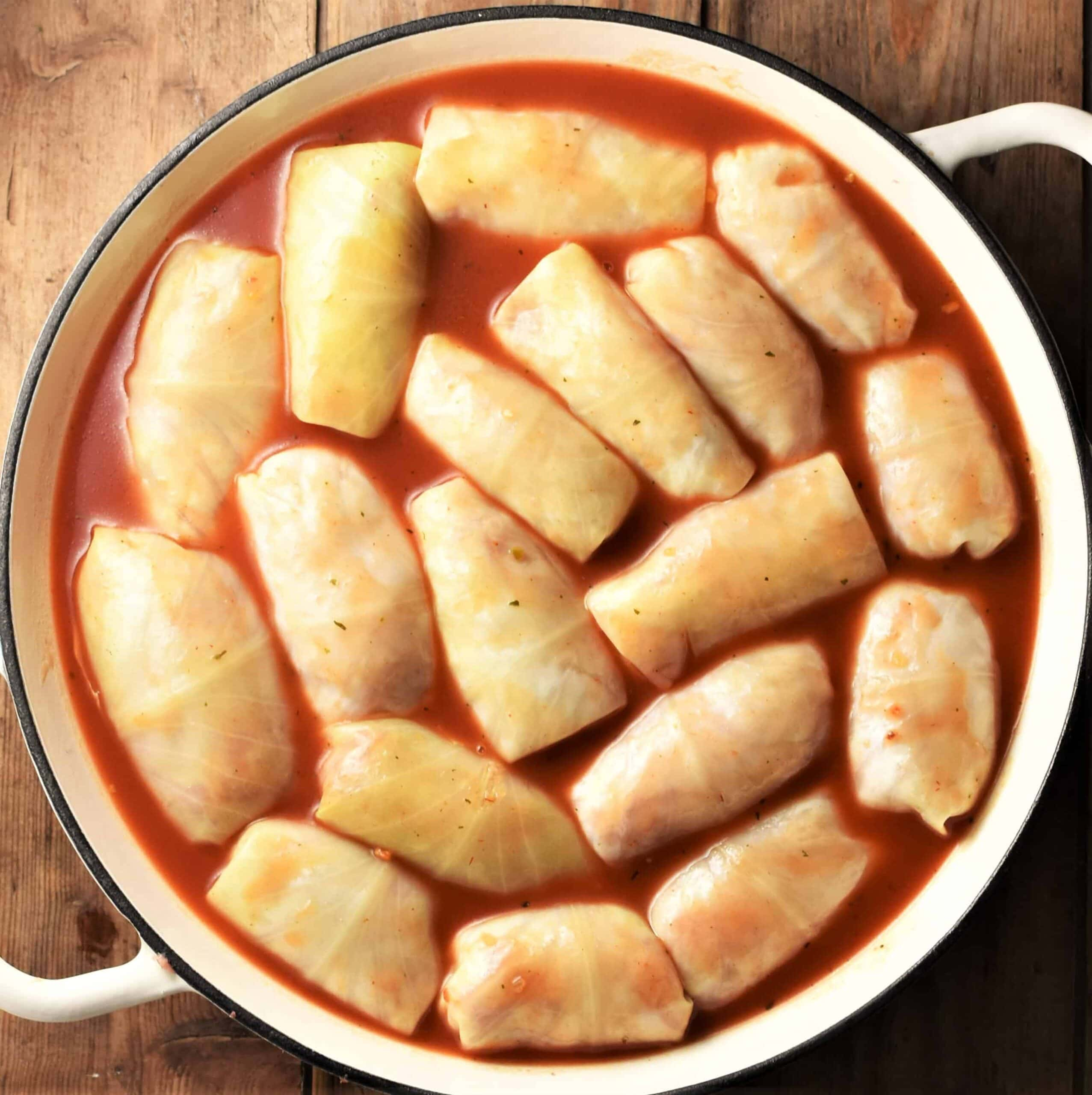 Cabbage rolls in tomato sauce inside large shallow yellow pan.