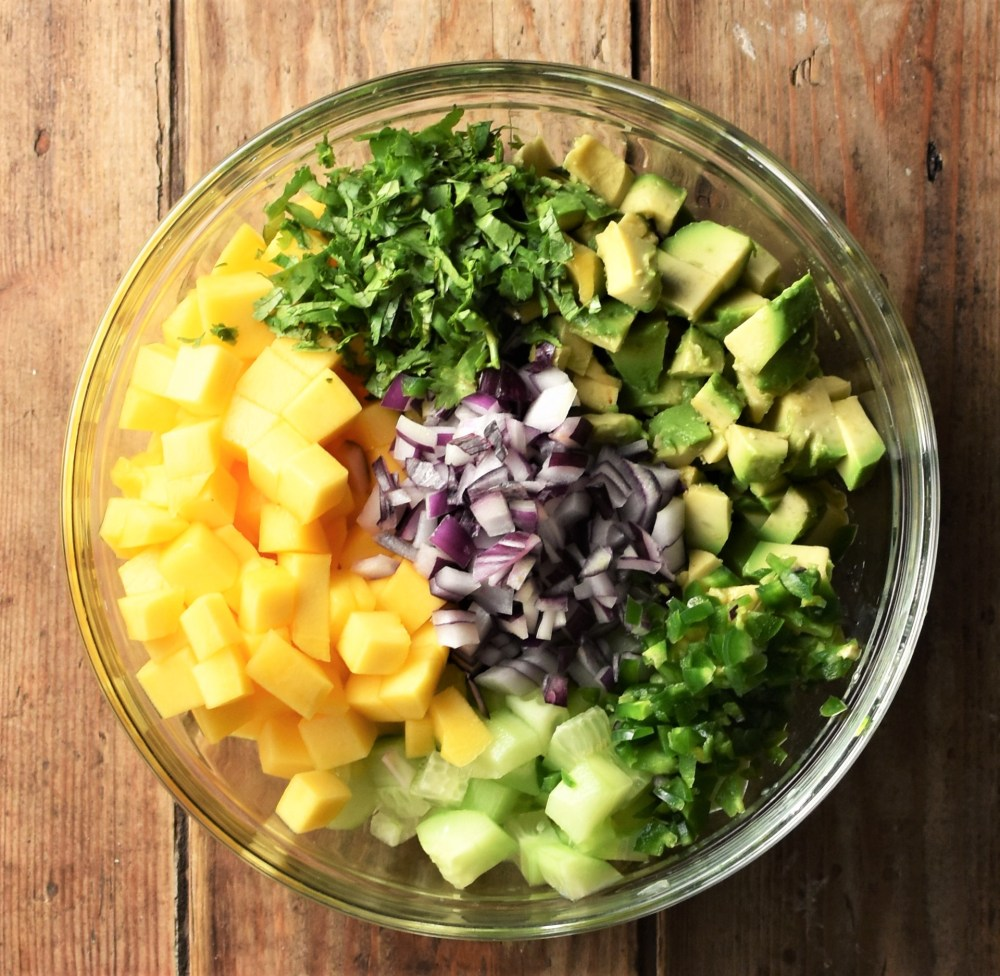 Chopped mango, avocado, cucumber, cilantro, red onion and chili pepper in b=mixing bowl.
