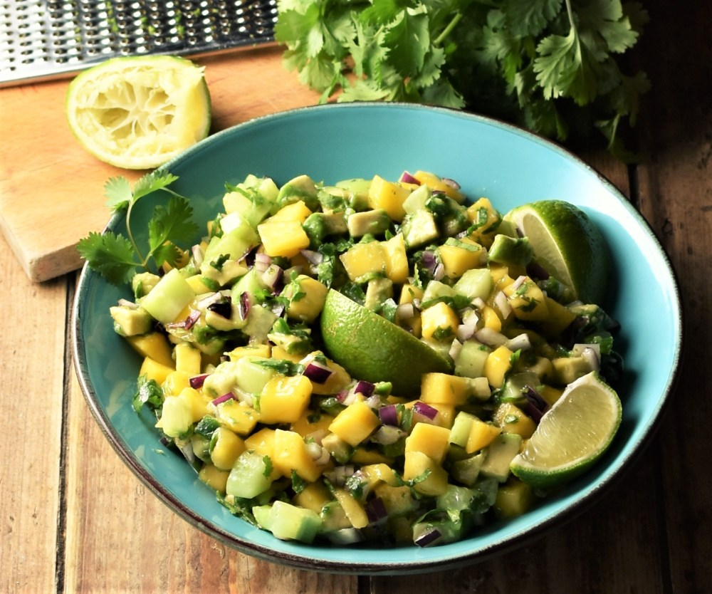 Chunky mango avocado salsa with lime wedges in large blue bowl with lime, zester and cilantro in background.