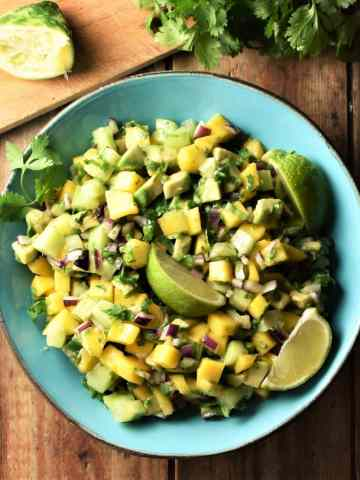 Mango, avocado and cucumber salsa with lime wedges in blue bowl with lime and cilantro in background.