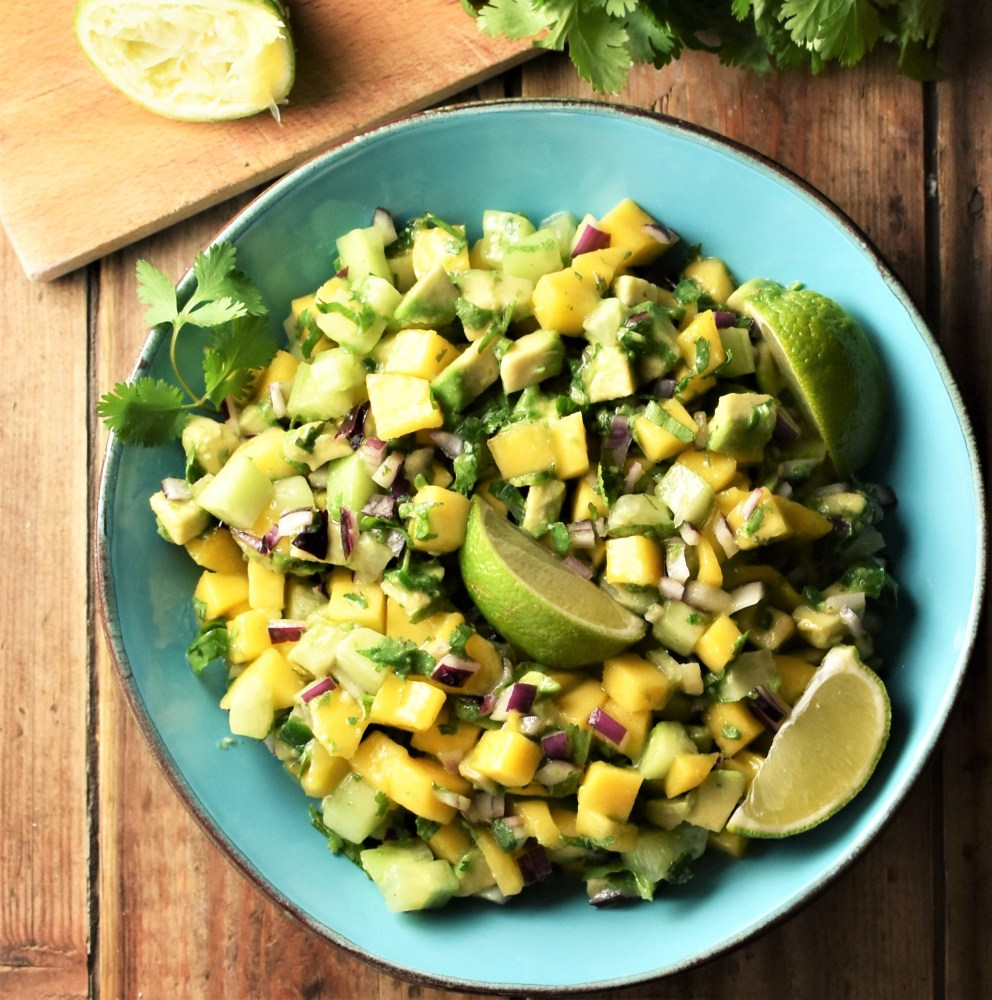 Chunky mango avocado salsa with lime wedges in blue bowl.