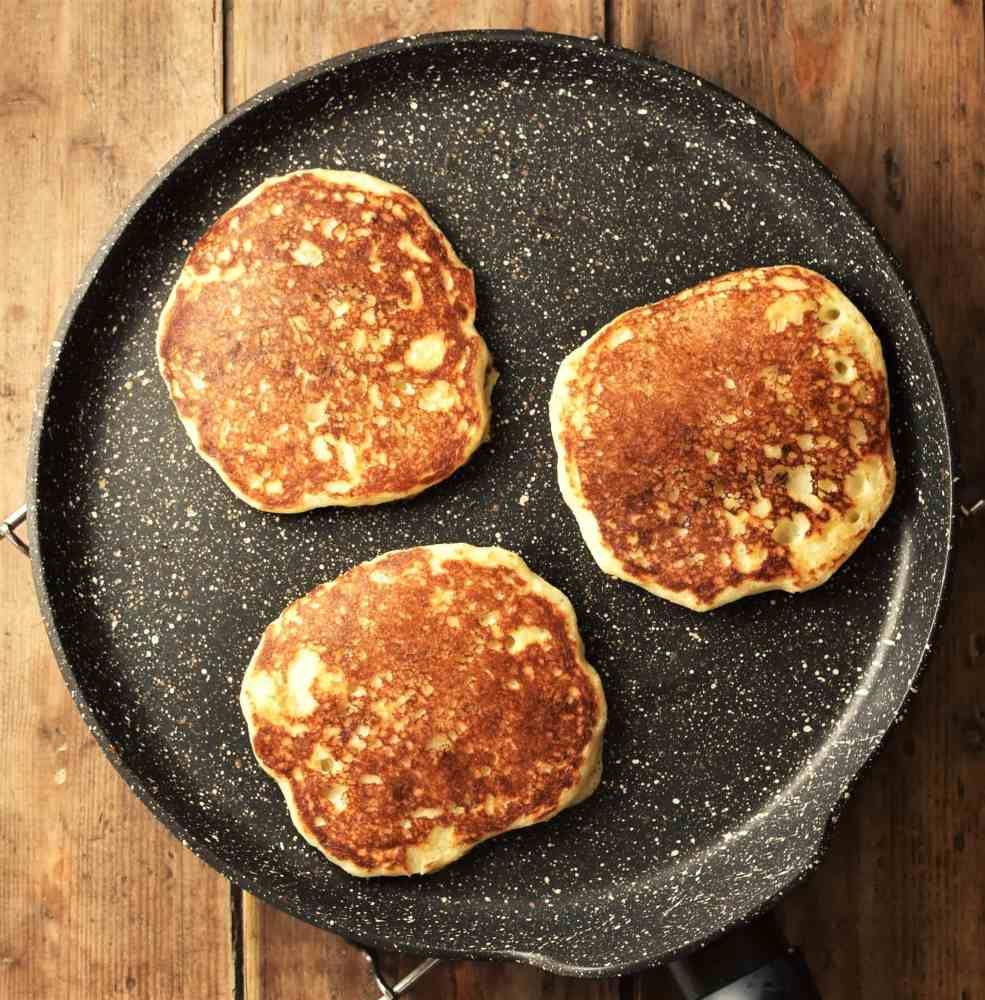 3 pancakes on top of frying pan.