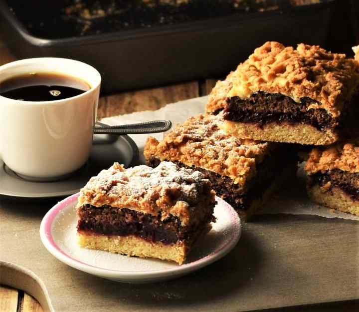 Slice of blackberry coffee cake on small plate with cake and cup of coffee in background.