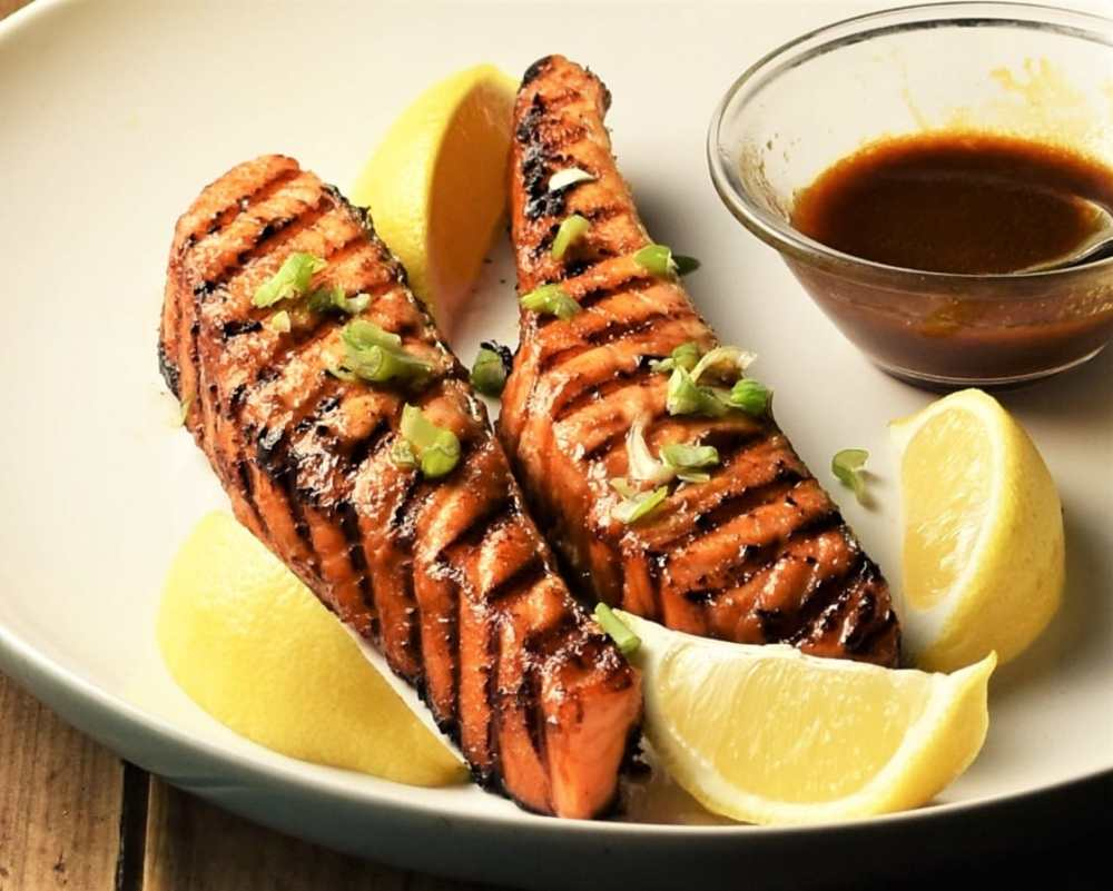 Close-up view of grilled marinated salmon with lemon wedges and hoisin sauce.