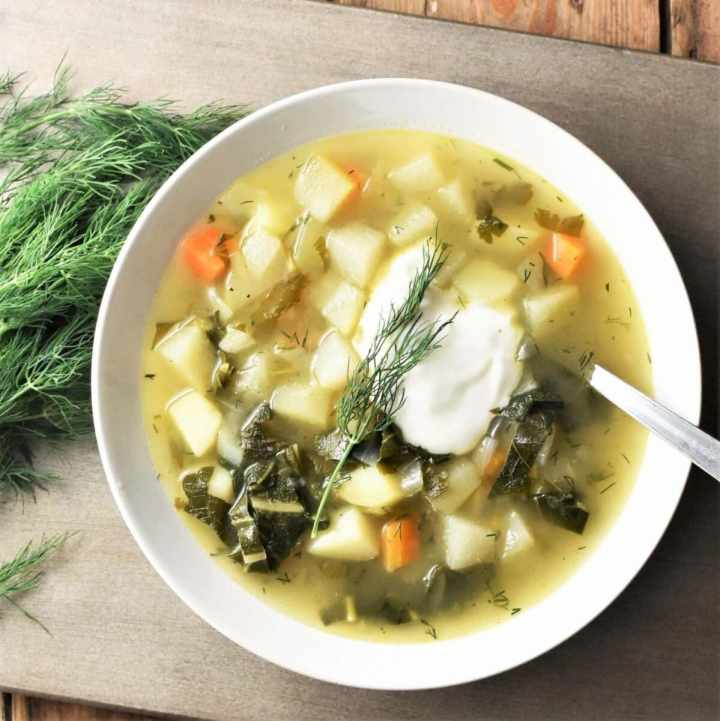 Chunky kohlrabi soup with vegetables and dollop of yogurt in white bowl with spoon and dill to the left.