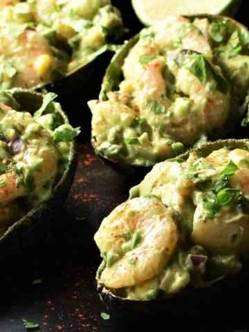 Close-up view of shrimp stuffed avocado halves.
