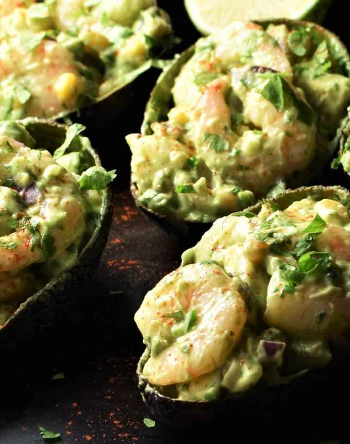 Close-up view of shrimp stuffed avocado halves.