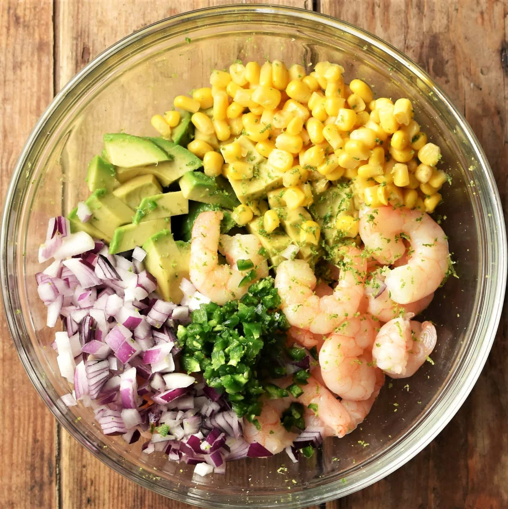 Shrimp, diced avocado, corn, chopped red onion and herbs in mixing bowl.
