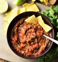Roasted tomato salsa in bowl with nachos and spoon, nachos, limes and herbs in background.