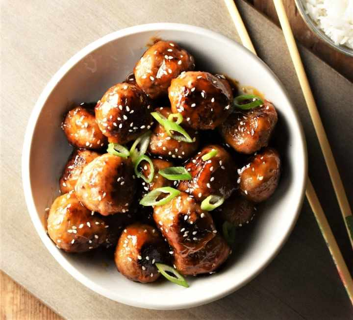 Top down view of meatballs in white bowl with chopsticks in background.