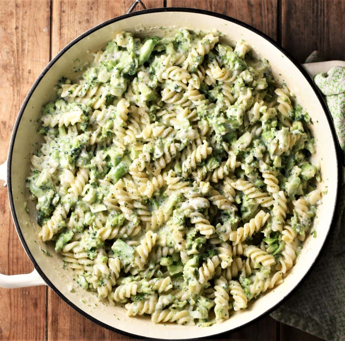 Pasta and broccoli in creamy sauce in large shallow white pan.