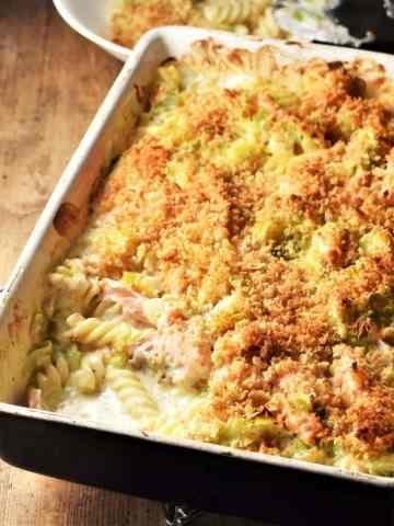 Side angle view of salmon pasta bake in rectangular dish.