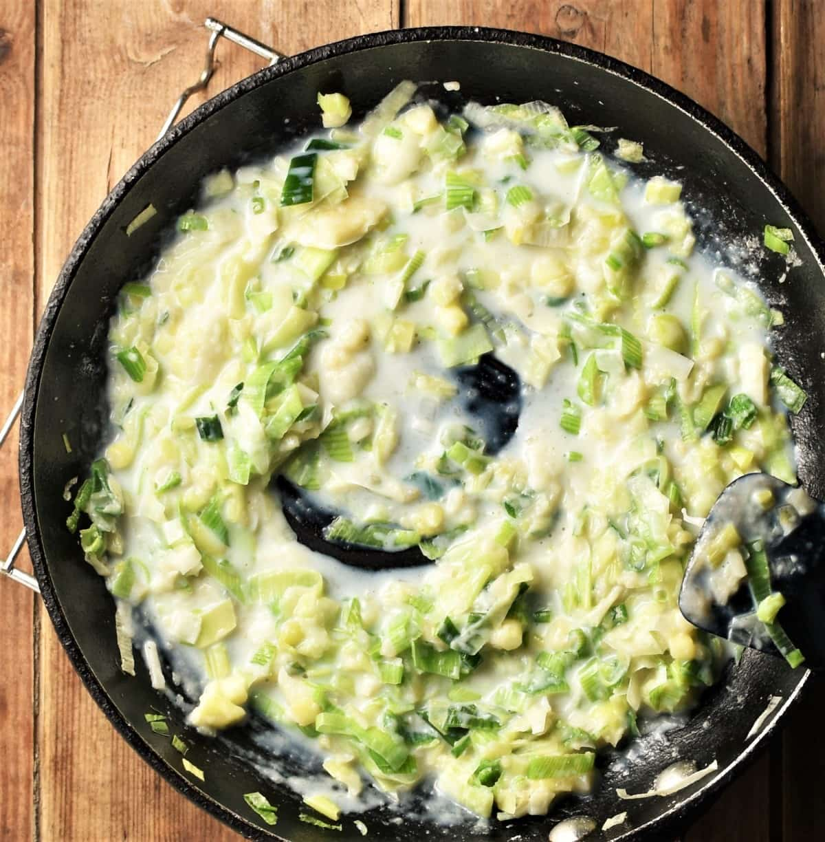 Chopped leek in creamy white sauce in pan.
