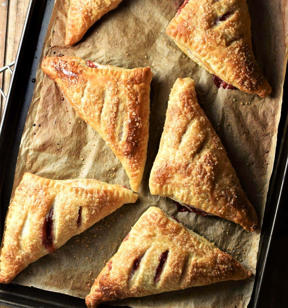 Baked strawberry turnovers on top of baking sheet lined with parchment.