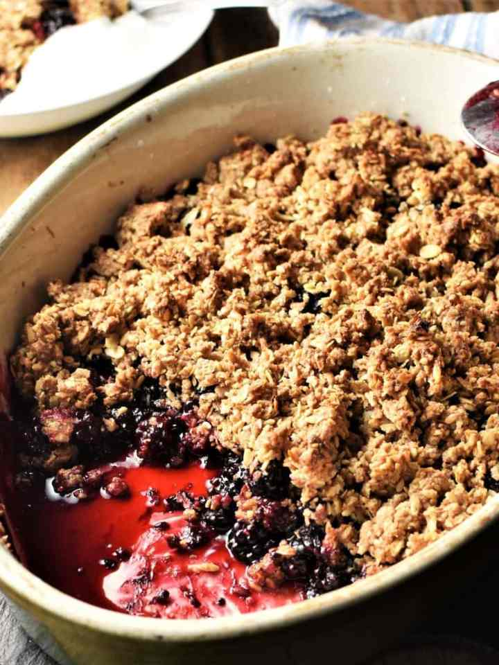 Side view of blackberry crumble in white oval dish.