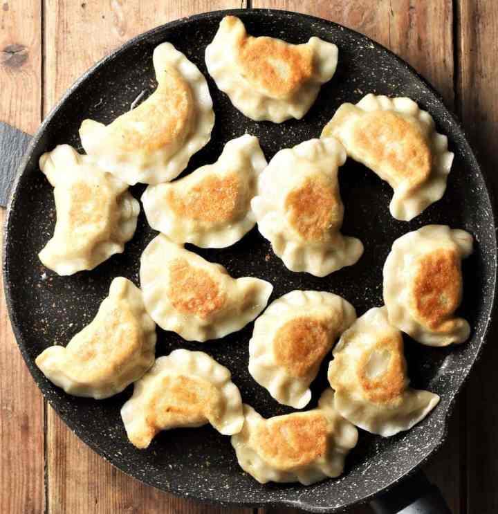 Fried pierogi in large pan.