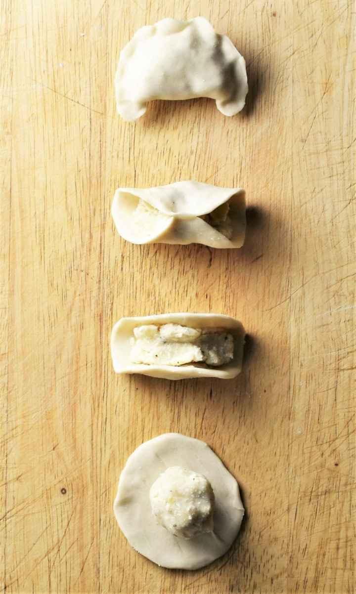 Making pierogi on top of wooden board.
