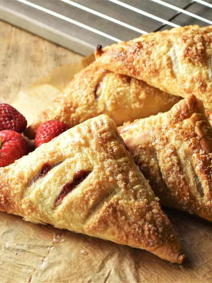 Side view of strawberry turnovers on top of parchment with fresh strawberries in background.