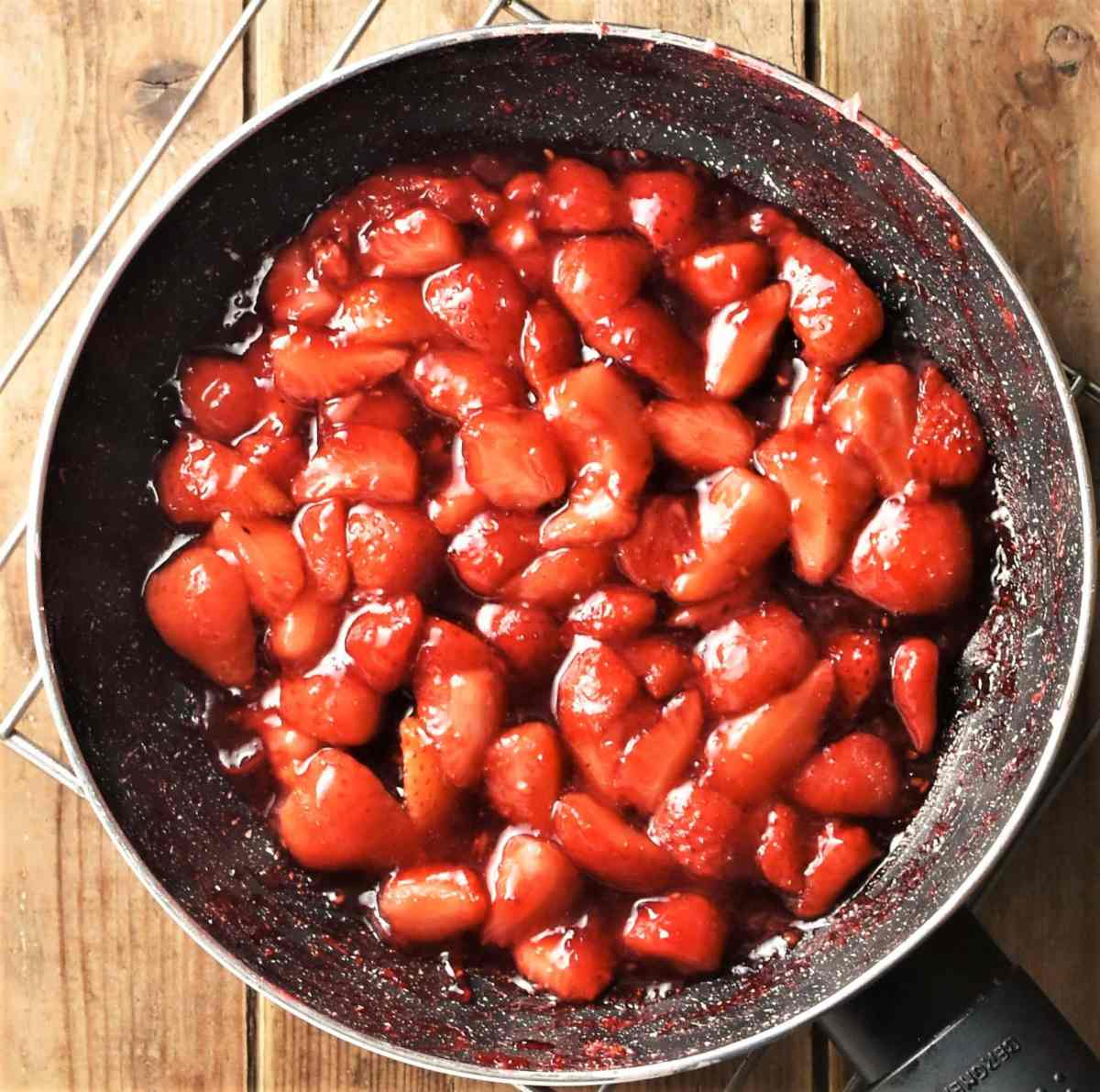 Cooked strawberries in pan.