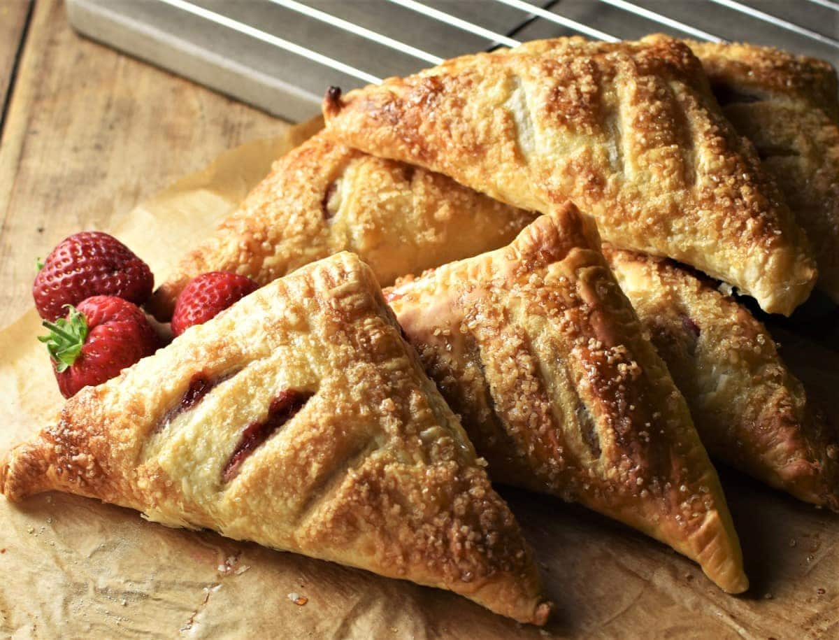 Side view of turnovers with fresh strawberries in background.