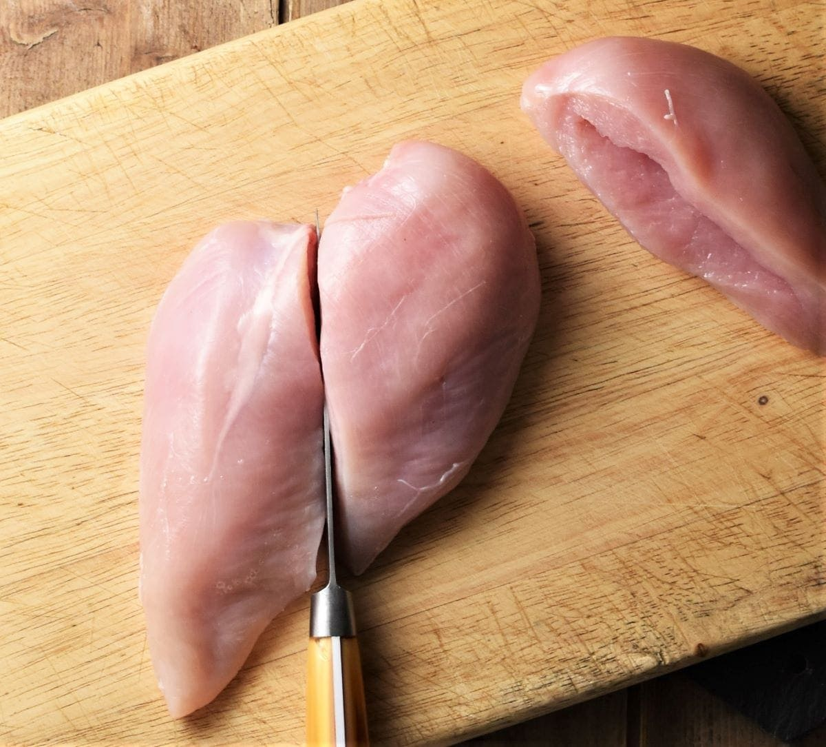 Cutting chicken breast on top of board.