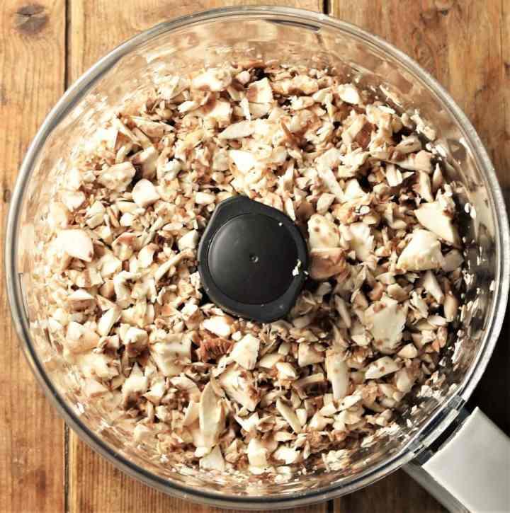 Chopped mushrooms in food processor bowl.