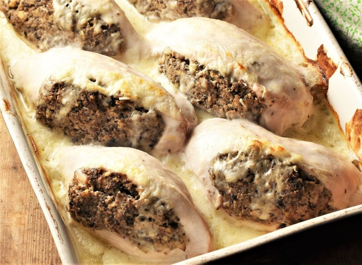 Close-up view of mushroom stuffed chicken breasts with sauce.