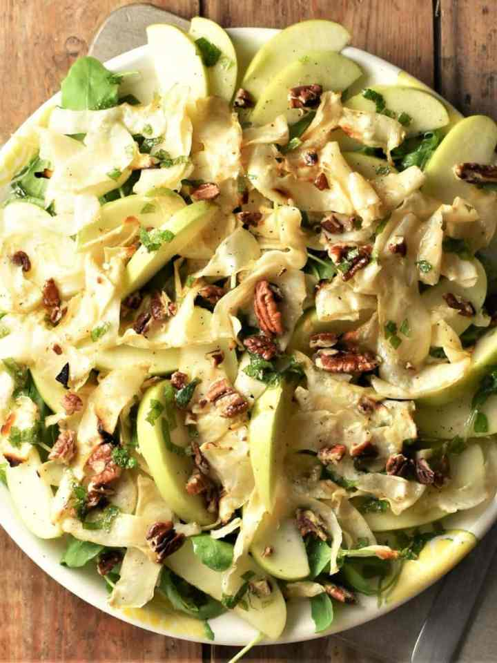 Top down view of roasted celery root salad with apple and pecans.