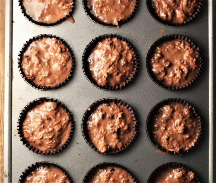Chocolate batter in paper cases in muffin pan.